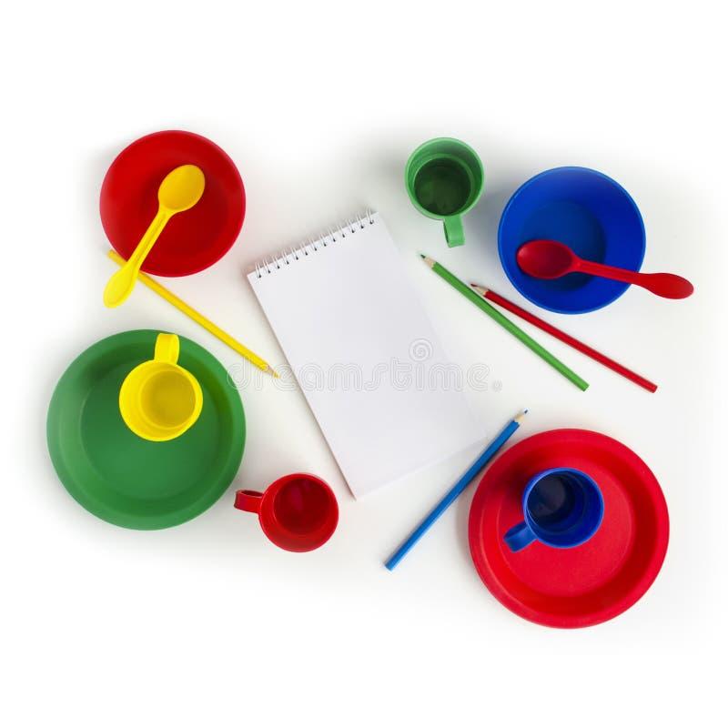 Stoviglie di plastica variopinte su fondo bianco con il blocco note e le matite Giocattolo dei bambini immagine stock libera da diritti
