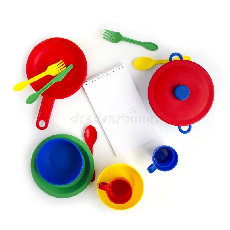 Stoviglie di plastica variopinte su fondo bianco con il blocco note e le matite Giocattolo dei bambini fotografia stock