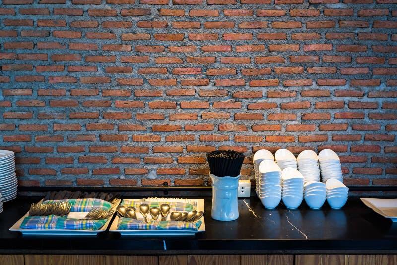 Stoviglie e terrecotte con il fondo del muro di mattoni in ristorante fotografia stock