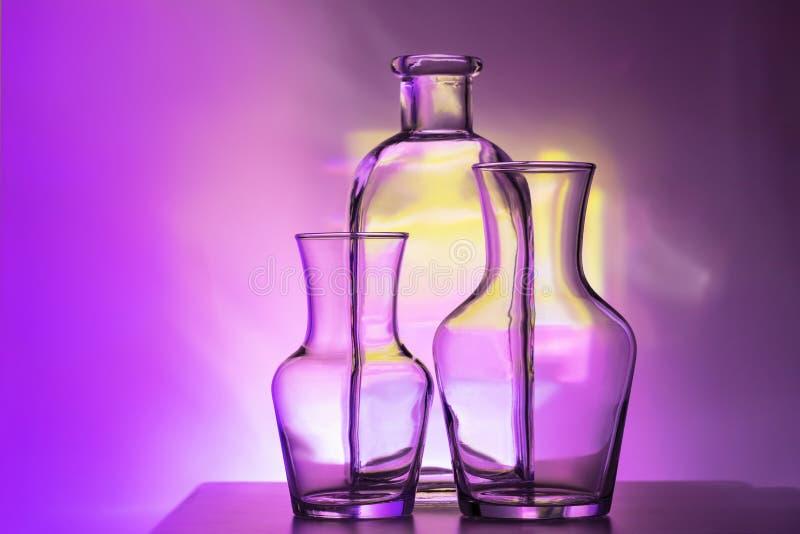 Stoviglie trasparenti di vetro - bottiglie delle dimensioni differenti, di tre pezzi su un bello colorato multi, giallo, lilla e fotografia stock