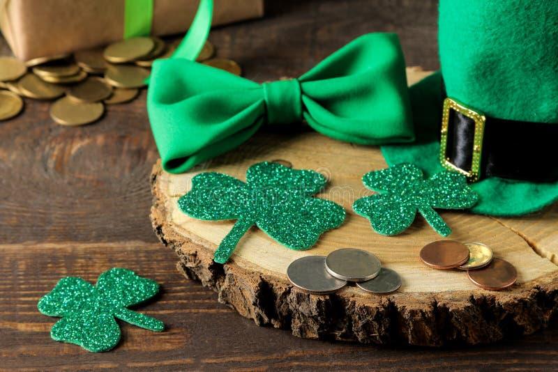 StPatrick ` s dzień Świętowanie Zielony leprechaun kapelusz, pieniądze, łęku krawat i koniczyna liść na brązu tle, obraz royalty free