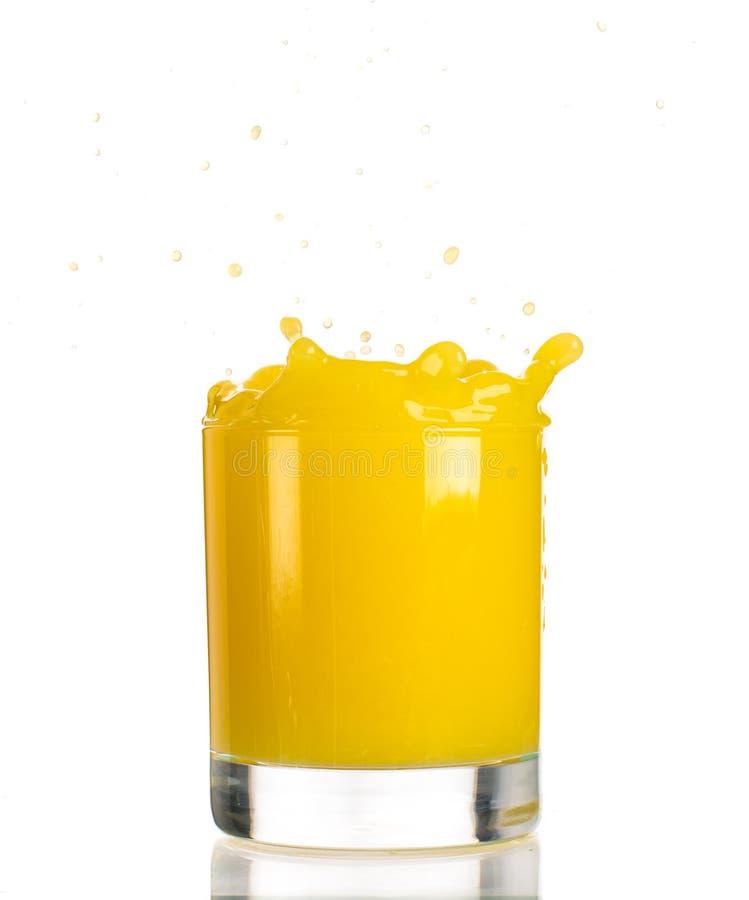 Strömender Orangensaft in ein transparentes Glas auf einem weißen Hintergrund stockfoto