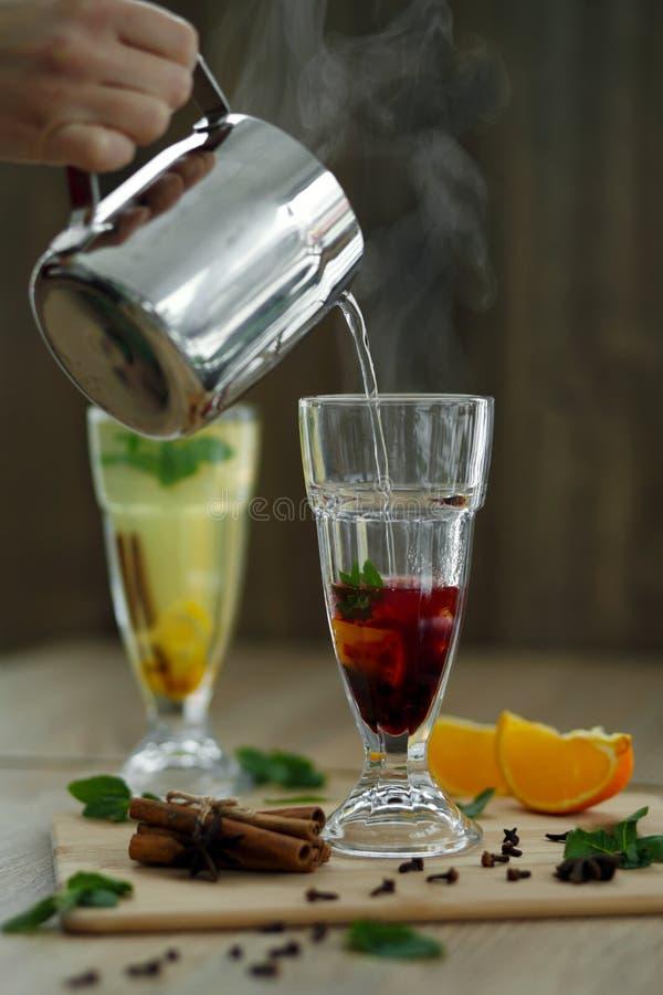 Strömendes heißes dämpfendes Wasser vom Stahltopf im Glas mit Vitamingetränk Winterheiße Saisongetränke stockfotografie