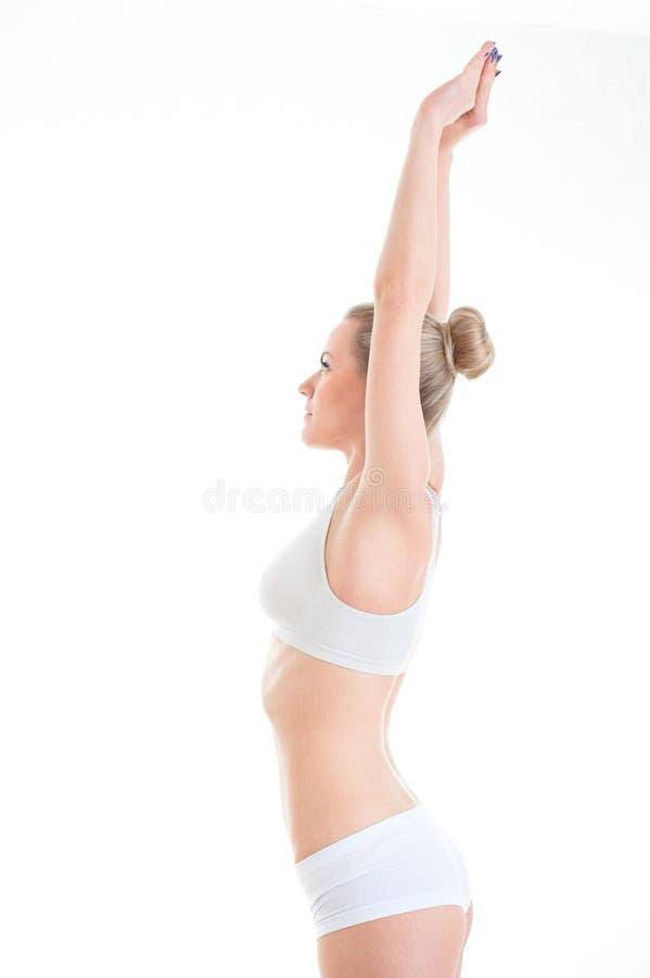 Sträcka den slanka och sportiga kvinnan i damunderkläder som isoleras på vit b arkivbild