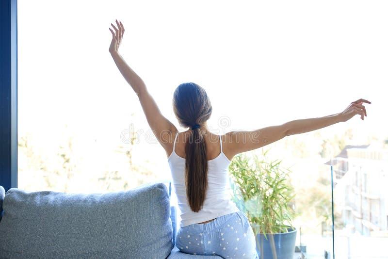Sträcka den unga kvinnan som hemma sitter på soffan arkivfoto
