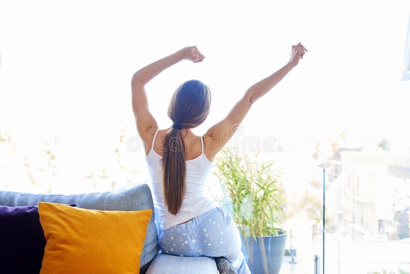 Sträcka den unga kvinnan som hemma sitter på soffan royaltyfri fotografi