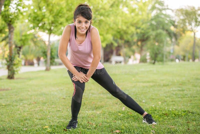 sträcker den iklädda sportswearen för denhaired flickan hennes ben, innan det startar till inkörd, parkerar royaltyfri foto