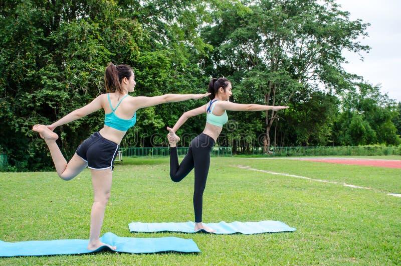 Sträckning av härlig ung kvinna två i utomhus- övning som ler lyckliga görande yogaelasticiteter, når att ha kört royaltyfri fotografi
