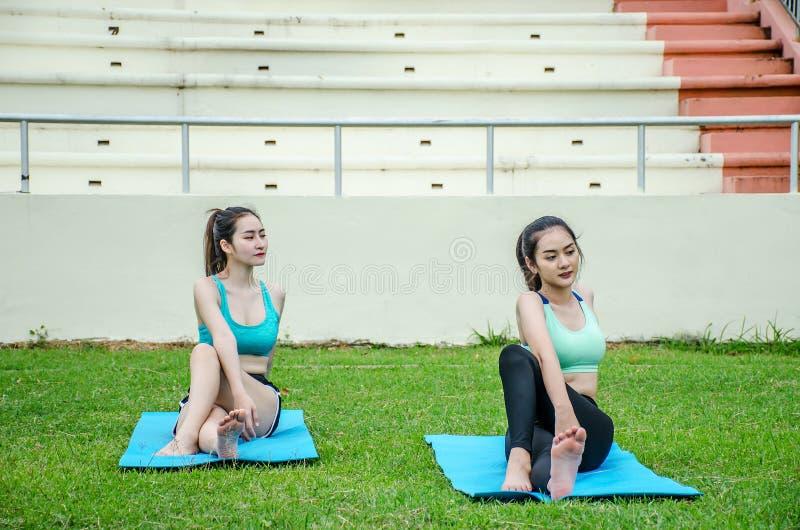 Sträckning av härlig ung kvinna två i utomhus- övning som ler lyckliga görande yogaelasticiteter, når att ha kört fotografering för bildbyråer