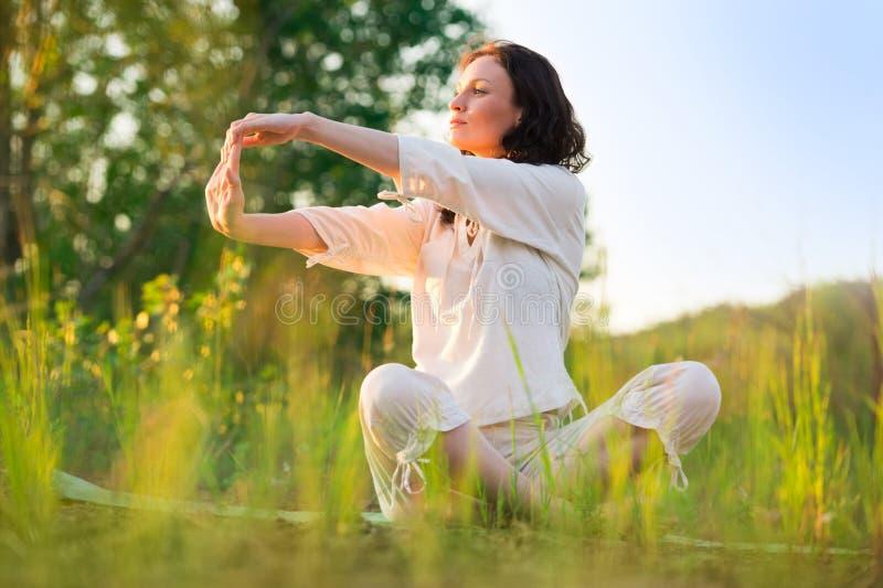 Sträckning av kvinnan i utomhus- övning som ler lycklig görande yoga royaltyfri fotografi