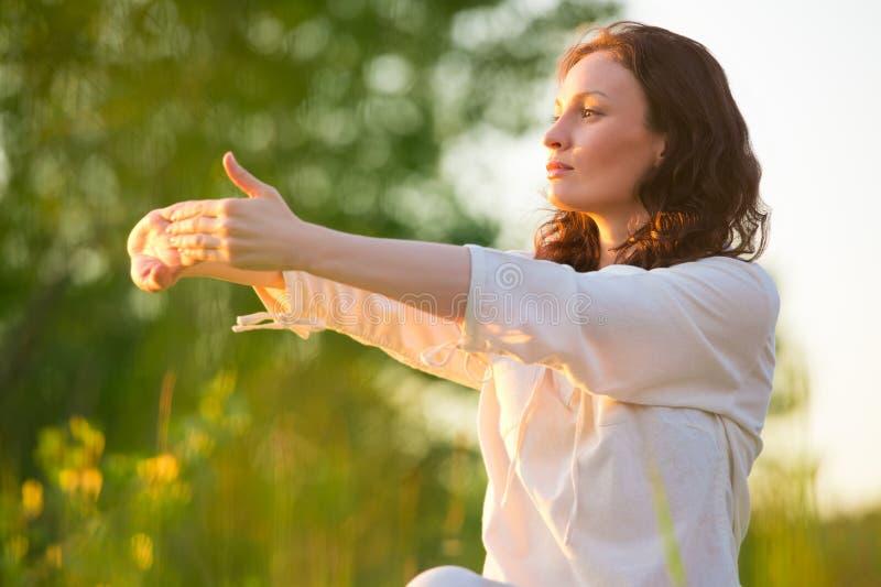 Sträckning av kvinnan i utomhus- övning som ler lycklig görande yoga fotografering för bildbyråer