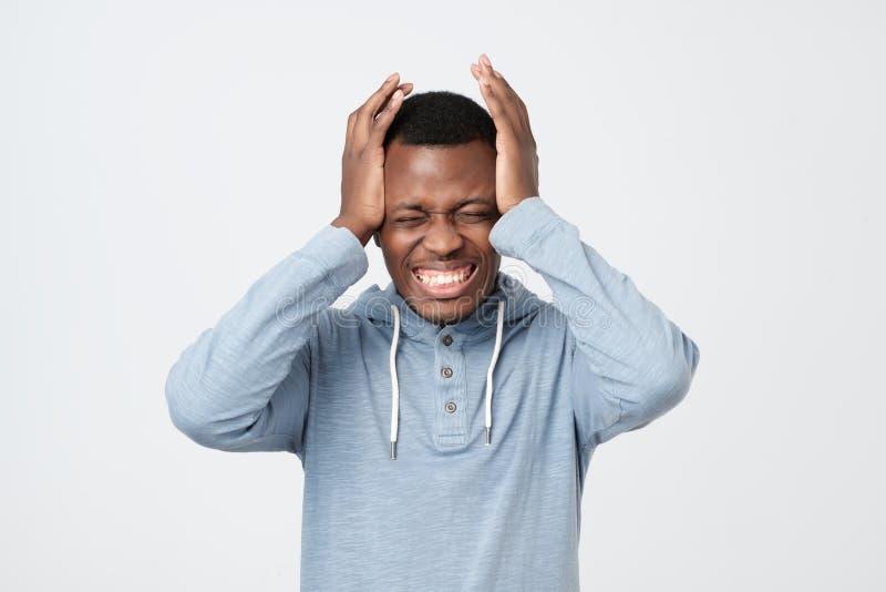Sträng huvudvärk för afrikansk amerikanmankänsla Han är att lida som rymmer hans huvud med båda händer royaltyfria foton
