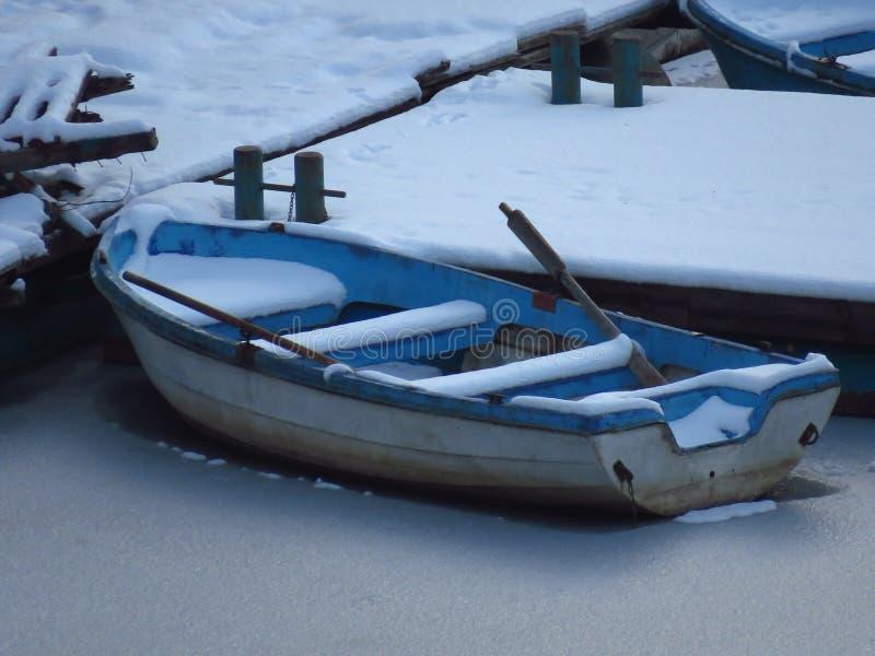 sträng vinter Ett blått fartyg som täckas med snö som nära frysas i vatten av den djupfrysta floden för kust, damm, sjö, hav arkivbilder