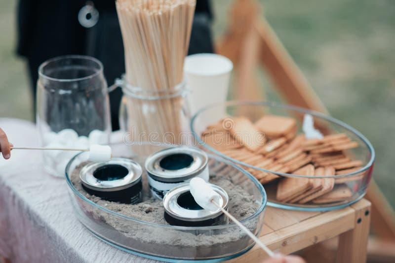 Strängde marshmallower på en liten brand på en tabell på ett gifta sig parti royaltyfri foto