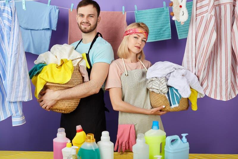 Strävsamma attraktiva par som rymmer korgen av tvätterit och ser kameran arkivfoto