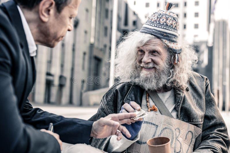 Stråla den imponerade grå färg-haired fattiga mannen som mottar lyckligtvis pengar arkivfoto
