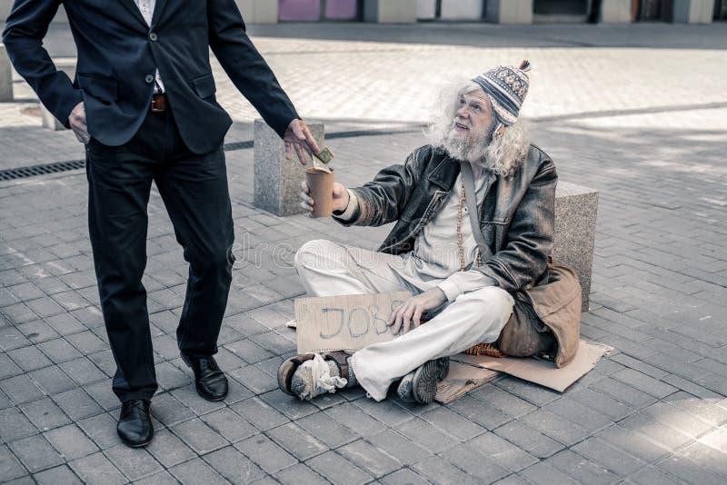 Stråla den långhåriga bedrövliga mannen som bär den tomma koppen och väntar på välgörenhet arkivfoton