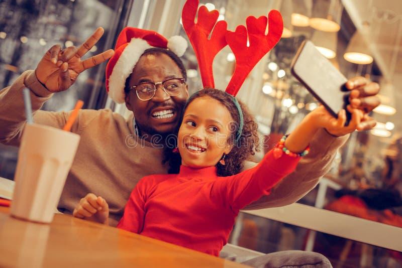 Stråla den moderna fadern som poserar för foto med hans gulliga flicka royaltyfria bilder