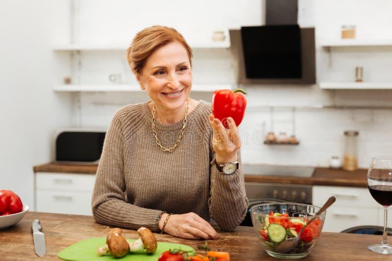 Stråla den mogna damen som lutar på trätabellen i kök fotografering för bildbyråer