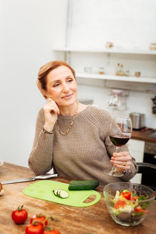 Stråla den snygga damen som rymmer exponeringsglas av vin, medan luta på tabellen arkivfoton