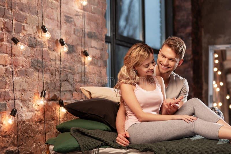 Stråla gladlynta par som spenderar afton i deras hemtrevliga sovrum royaltyfria foton
