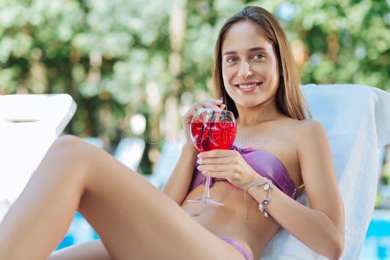 Stråla kopplad av kvinnakänsla, medan dricka jordgubbecoctailen royaltyfri fotografi