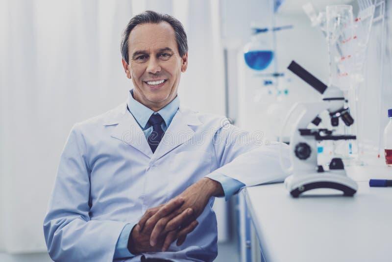 Stråla läkaresammanträde nära hans funktionsdugliga tabell royaltyfria foton
