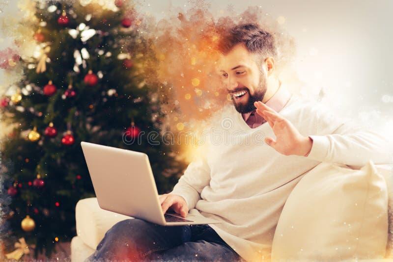 Stråla mannen som har video pratstund med hans vänner som gratulerar med nytt år royaltyfria foton