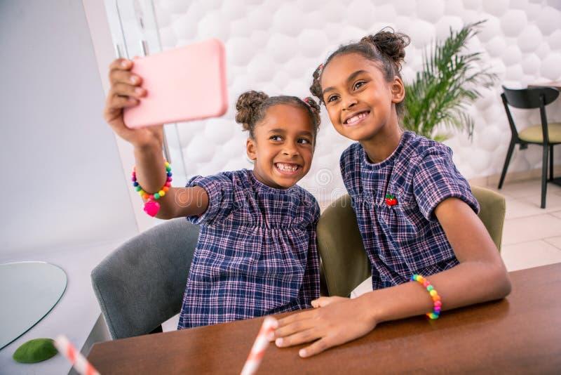 Stråla mer ung sibling som ler ha i huvudsak hennes första smartphone royaltyfria bilder