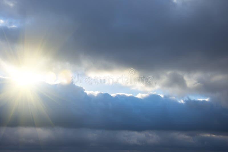 Strålar av ljus som skiner till och med mörka moln, dramatisk himmel med molnet royaltyfria foton