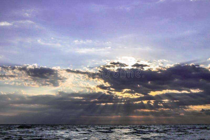 Strålar av solen som bryter till och med molnen royaltyfria bilder