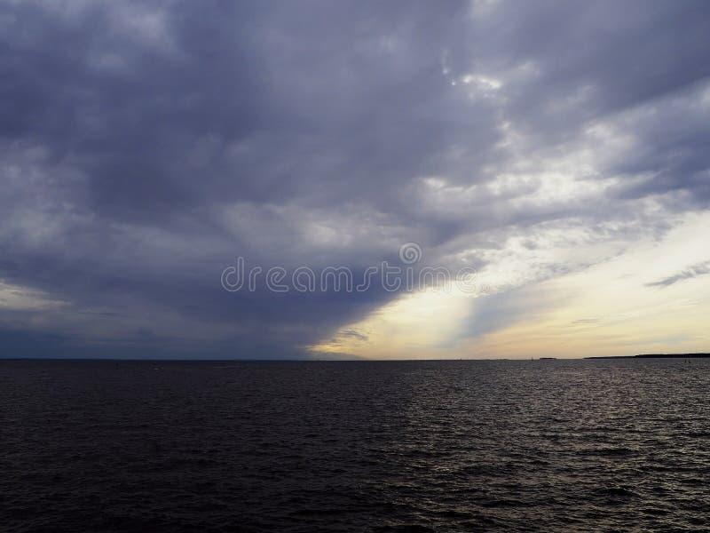Strålar av solen till och med stormmoln över havet arkivbild
