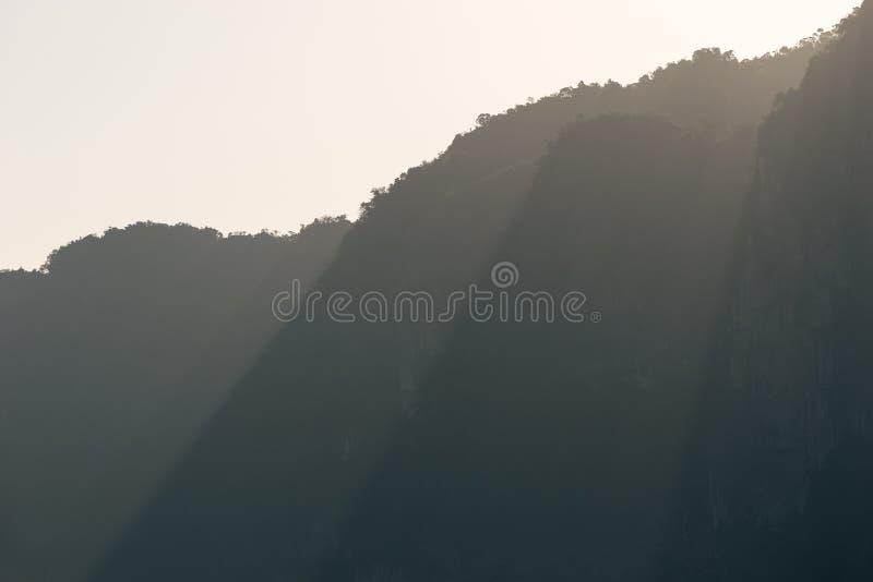 Strålar av solljus faller till och med maxima av bergkonturer i den disiga morgonen royaltyfri fotografi
