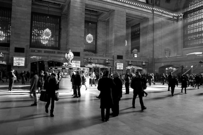 Strålar av solljus inom av den Grand Central stationen med folk som går i rusatiden arkivfoto