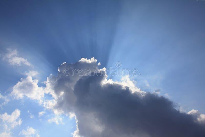 strålar bak den blåa oklarhetsskysunen arkivfoto