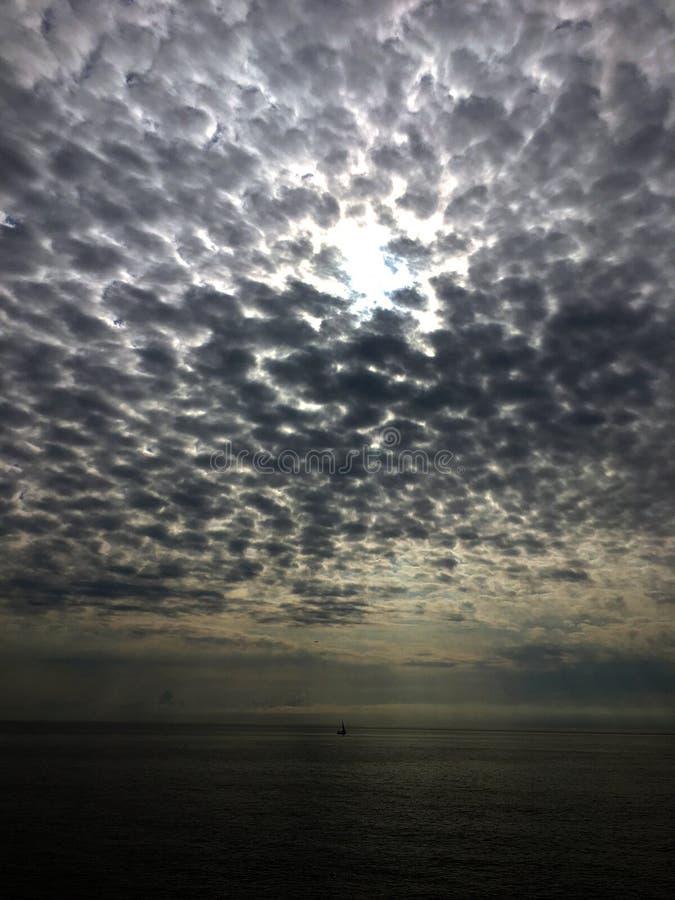 Strålar för molnig himmel och solöver havet med ett fartyg royaltyfria foton
