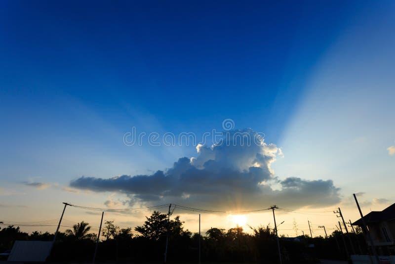 Stråle av solljus till och med molnet på solnedgånghimmel royaltyfria foton