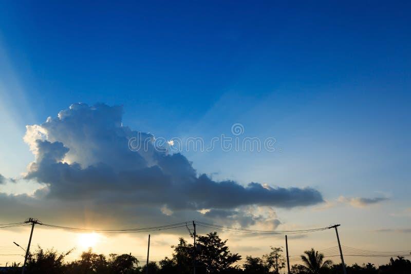 Stråle av solljus till och med molnet på solnedgånghimmel arkivfoto