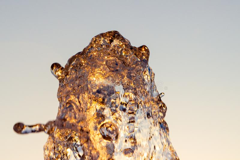 Strålen för Ð-¡ loseup av vatten från en springbrunn som slås upp mot en blå himmel, droppar av vatten, skimrar i solen, och strå arkivfoto