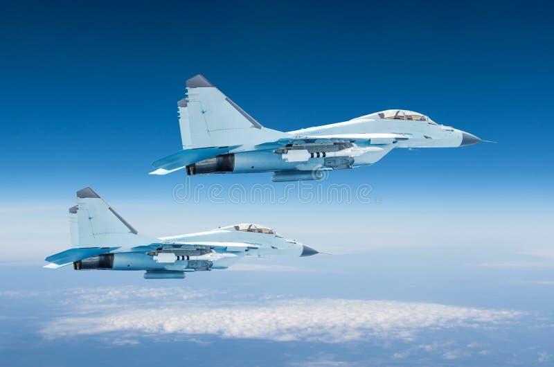 Strålflygplan för två militärt kämpar på hög höjd, stridbeskickningoperation som högt flyger i himlen arkivbilder