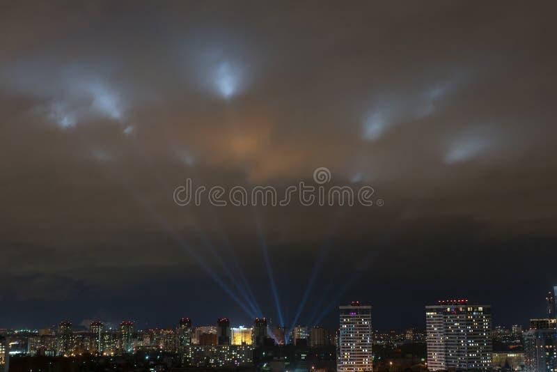 Strålkastare skiner i natthimlen över staden royaltyfri fotografi