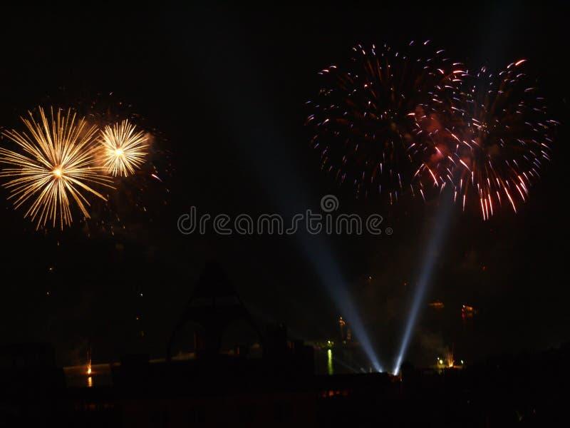 Strålkastare som exponerar stora färgrika stadsfyrverkerier mot bakgrunden av natthimlen royaltyfri bild
