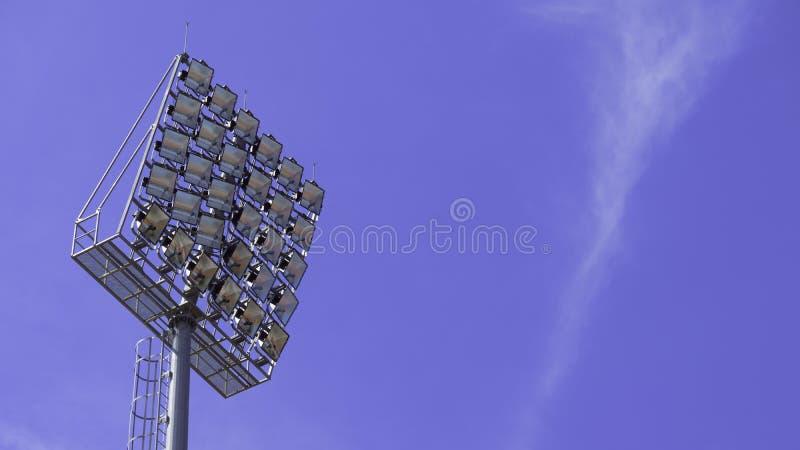 Str?lkastare st?r h?gt med en metallpol f?r sportarenan Installerat runt om fotbollsarena bl? sky f?r bakgrund arkivfoto