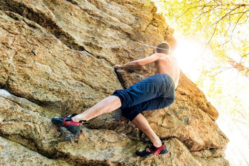 Strålklättrare som klättrar upp på ett klick på skogen Lågvinkeln av en stark bergsbestigare som hänger fritt på sten med arkivfoto