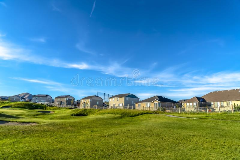 Strålningsblå himmel och moln över hus och golfbana på en solig dag royaltyfri bild