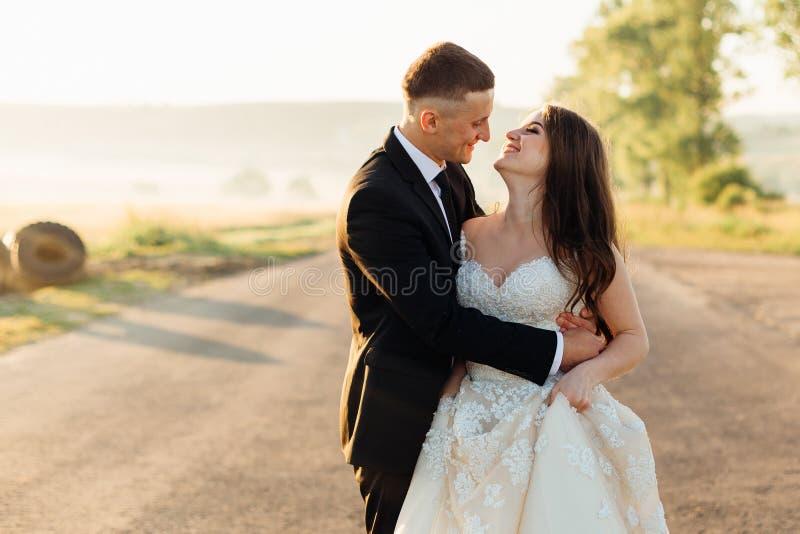 Strålningsbrudgummen beundrar hans brudwhle som kramar på aftonvägen royaltyfri foto