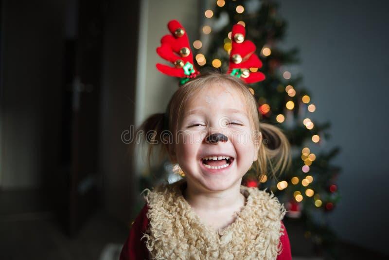 Strålningsflicka i en hjort i bakgrunden av julgranen hemma lycklig skrattande barn kul kille fotografering för bildbyråer