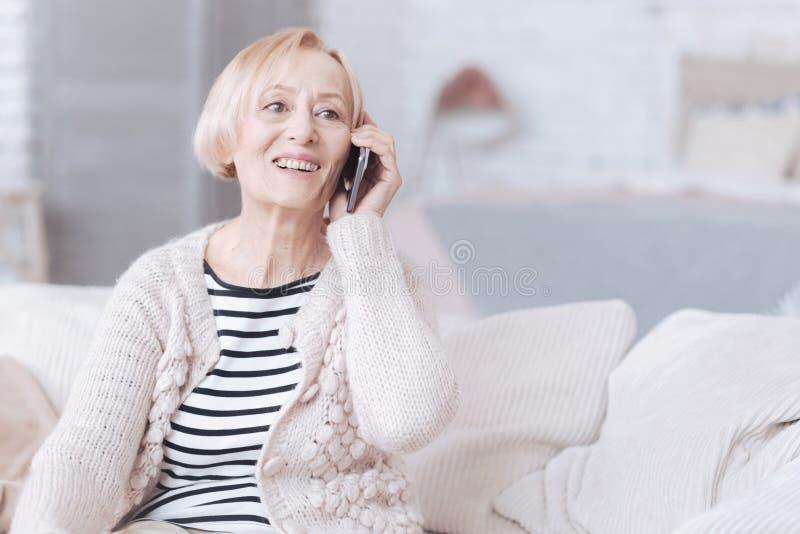 Strålningshög dam som hemma talar på telefonen royaltyfri foto