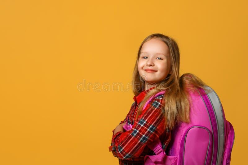 Strålningskänslig av en liten flicka på en gul bakgrund Barnet har en ryggsäck bakom ryggen Tillbaka till skolan royaltyfri fotografi