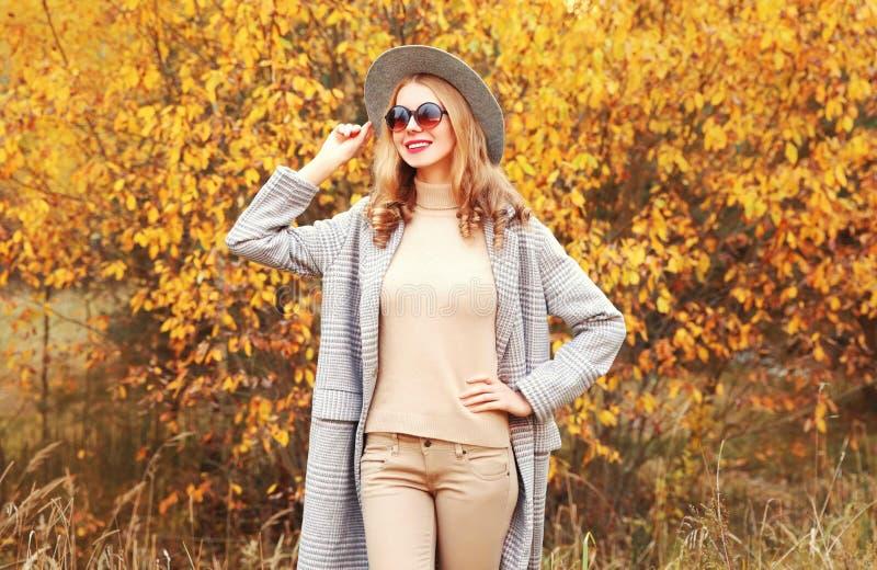 Strålningskänslig, glad leende kvinna med grå rock, rund hatt på gula blad royaltyfri foto